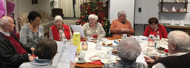 Ältere Menschen sitzen zusammen und singen Weihnachtlieder - Ihr Ambulanter Pflegedienst Harmonie GmbH in Hamm.